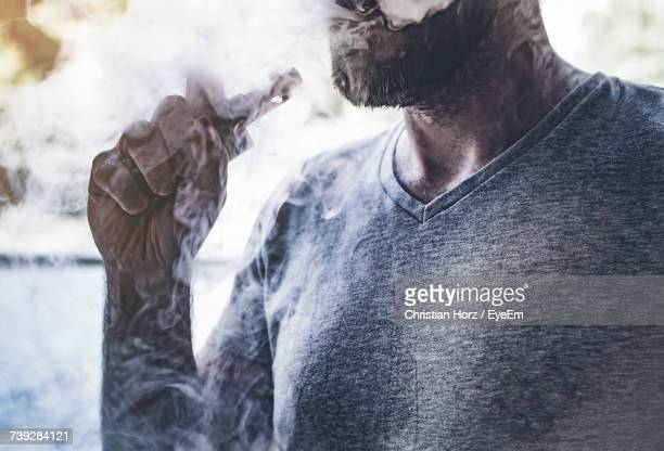 midsection of man smoking e-cigarette - vaping stock photos and pictures