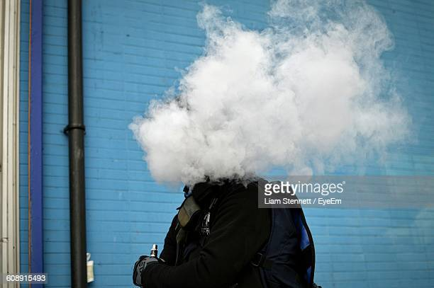 Midsection Of Man Smoking Hookah Against Blue Wall