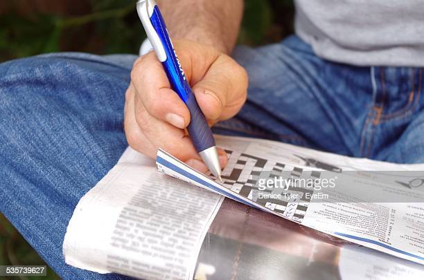 Midsection Of Man Solving Crossword On Newspaper