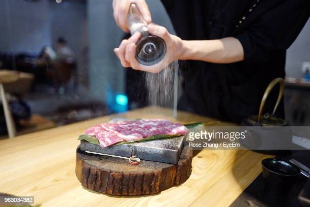 midsection of man sprinkling salt on raw meat at kitchen - salt and pepper shakers stock pictures, royalty-free photos & images