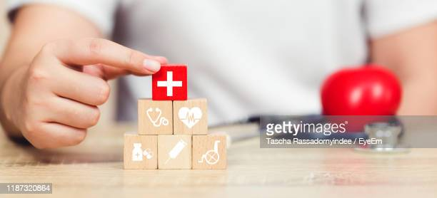 midsection of man stacking wooden block with symbol on table - medical symbol stock pictures, royalty-free photos & images