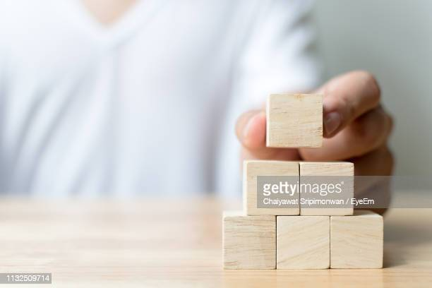 midsection of man stacking wooden toy blocks at table - toy block stock pictures, royalty-free photos & images