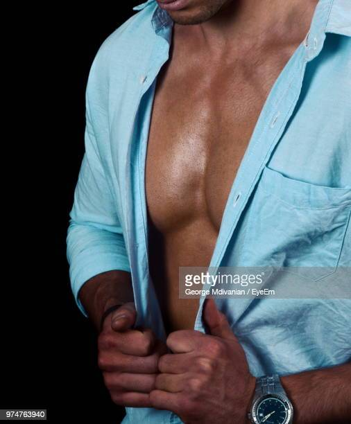 midsection of man standing against black background - male torso stock photos and pictures
