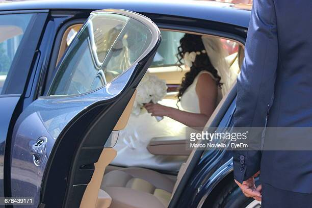 Midsection Of Man Standing Against Bride Sitting In Car