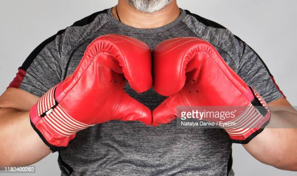 midsection of man standing against red wall - beating heart stock pictures, royalty-free photos & images