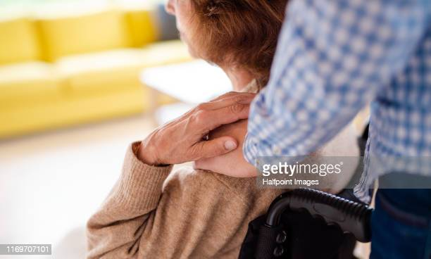 a midsection of man standing behind woman in wheelchair indoors at home. - marryornot stock pictures, royalty-free photos & images