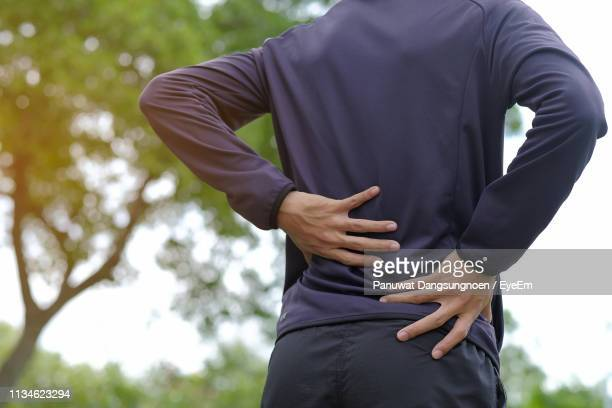 midsection of man suffering from backache - backache stock pictures, royalty-free photos & images