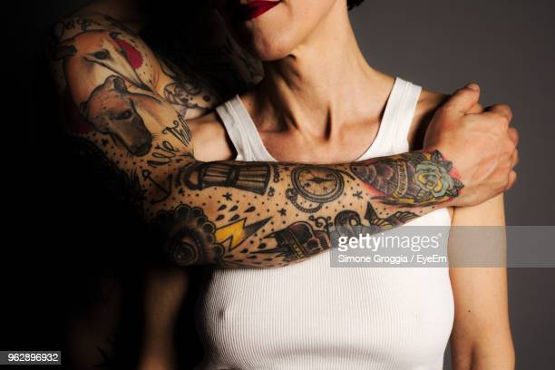 Midsection Of Man Tattooed Hand Over Woman Against Black Background