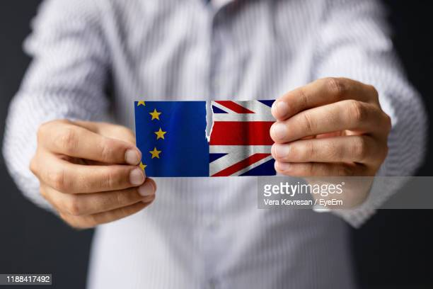midsection of man tearing flags - brexit stock pictures, royalty-free photos & images