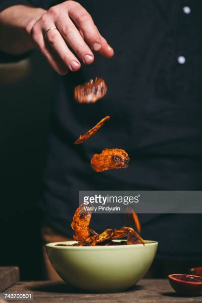 Midsection of man throwing roasted orange peel in bowl at table