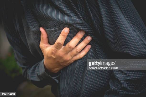 midsection of man touching breast while standing at park - heart attack stock pictures, royalty-free photos & images