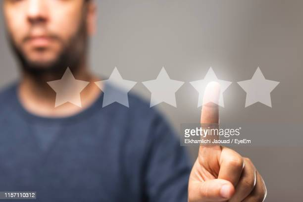 midsection of man touching star shapes against gray background - valutazione foto e immagini stock