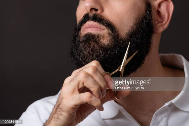 midsection of man trimming beard against black background - solo un uomo foto e immagini stock