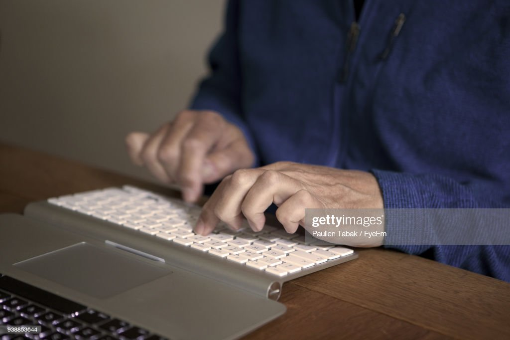 Midsection Of Man Typing On Keyboard At Table : Stockfoto