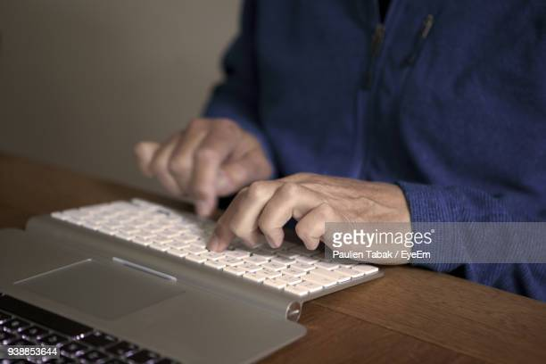 midsection of man typing on keyboard at table - paulien tabak stock pictures, royalty-free photos & images