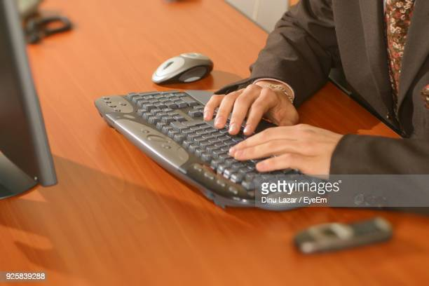 Midsection Of Man Using Computer On Desk At Office