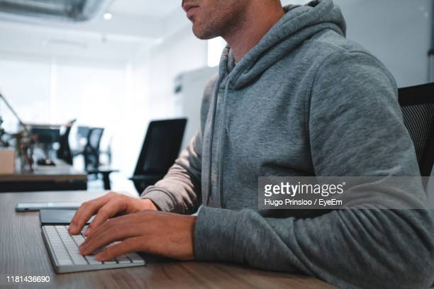 midsection of man using computer on desk in office - prinsloo photos et images de collection