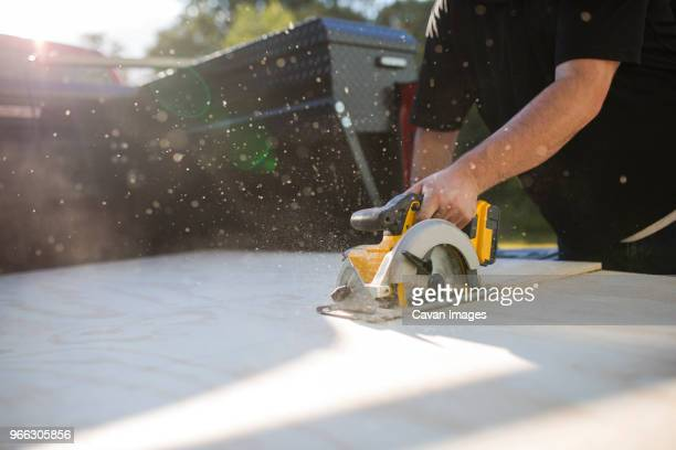 midsection of man using electric saw while sawing wooden plank in yard - circular saw stock photos and pictures