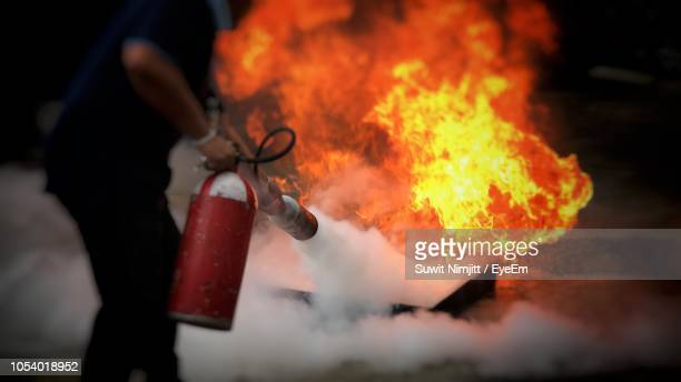 midsection of man using fire extinguisher - fire extinguisher stock photos and pictures