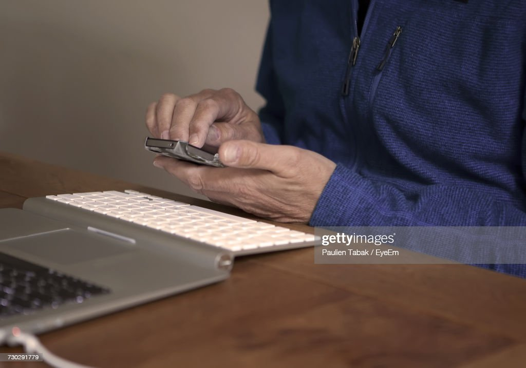 Midsection Of Man Using Mobile Phone By Laptop On Table : Stockfoto