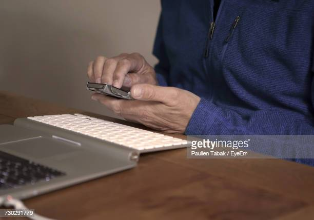 midsection of man using mobile phone by laptop on table - paulien tabak 個照片及圖片檔