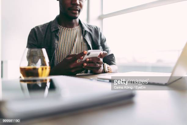 Midsection Of Man Using Mobile Phone In Office