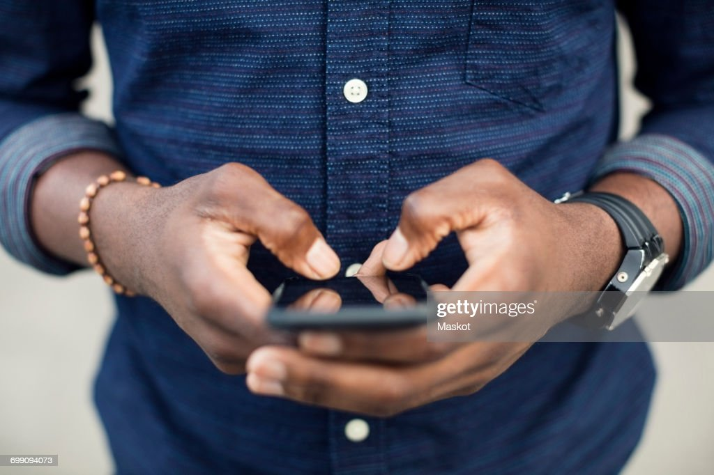 Midsection Of Man Using Mobile Phone Stock Photo Getty Images
