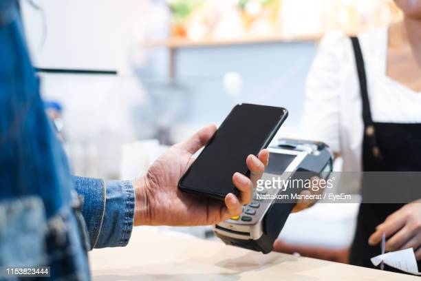 midsection of man using phone while paying at caf� - contactless payment stock pictures, royalty-free photos & images