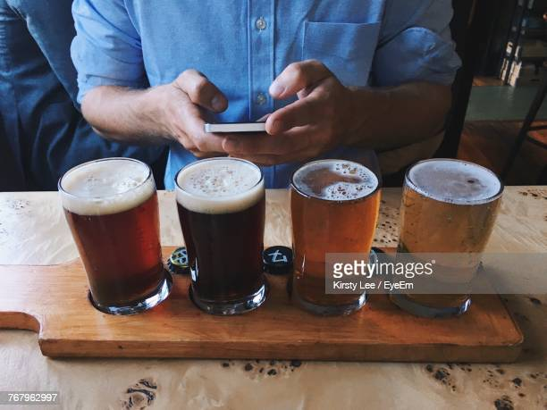 Midsection Of Man Using Phone While Standing By Beer Glasses On Tray