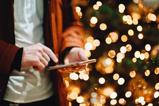 Midsection Of Man Using Smart Phone Against Illuminated Christmas Tree - gettyimageskorea
