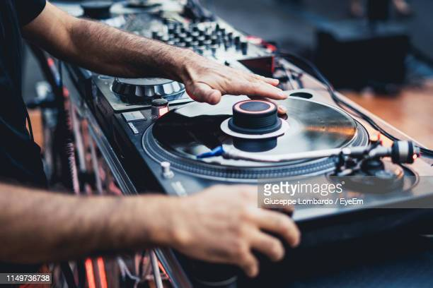 midsection of man using turntable and sound mixer - dj photos et images de collection