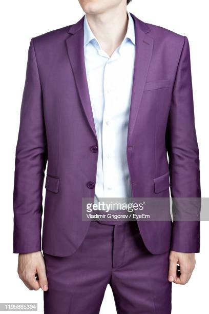 midsection of man wearing blazer standing against white background - purple suit stock pictures, royalty-free photos & images