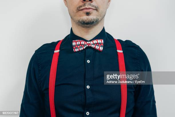 midsection of man wearing bow tie against white background - suspenders stock pictures, royalty-free photos & images