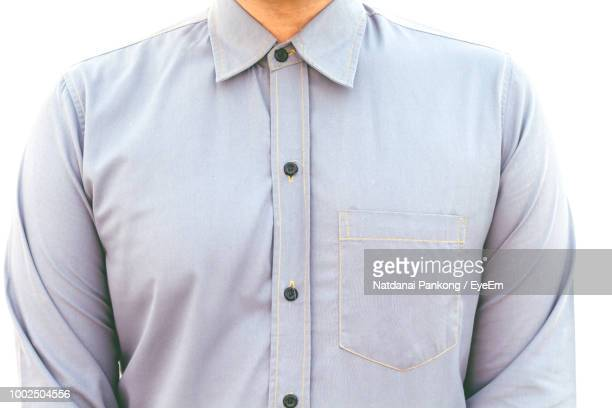 midsection of man wearing button down shirt against white background - camicia foto e immagini stock