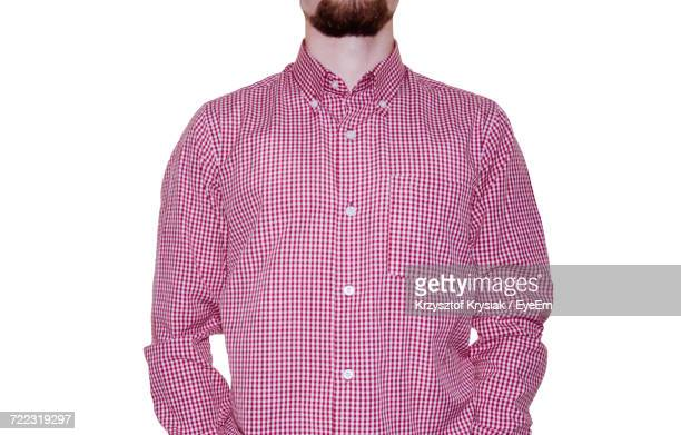 Midsection Of Man Wearing Checked Patterned Shirt Against White Background
