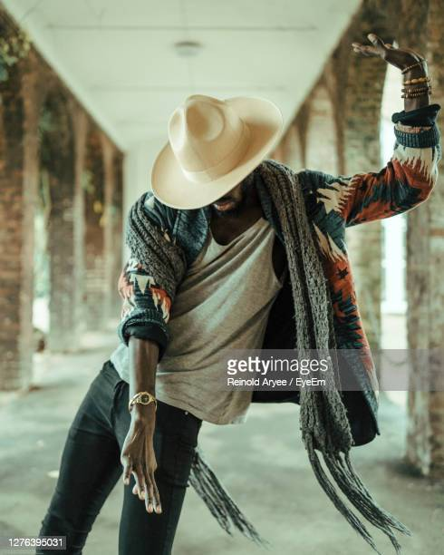 midsection of man wearing hat standing against wall in city - dancing stock pictures, royalty-free photos & images
