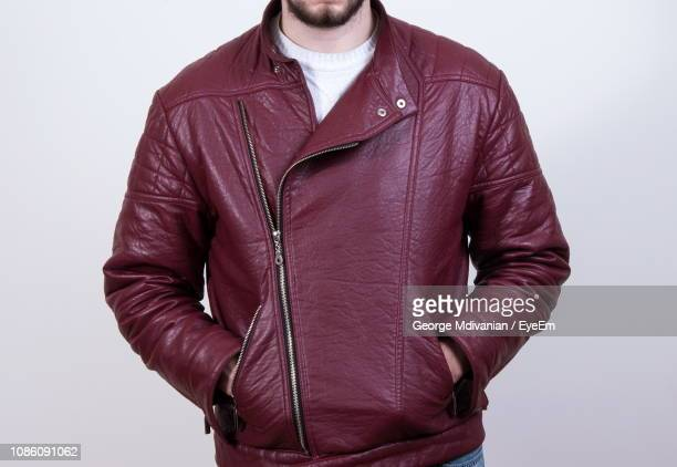 midsection of man wearing leather jacket while standing against white background - brown jacket stock pictures, royalty-free photos & images