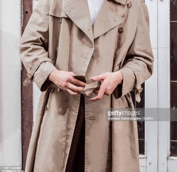 midsection of man wearing long coat - ロングコート ストックフォトと画像