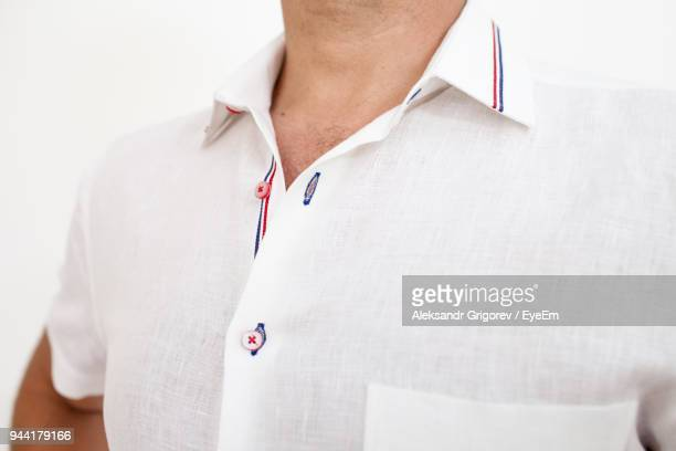 midsection of man wearing shirt against white background - cuello parte de la vestimenta fotografías e imágenes de stock