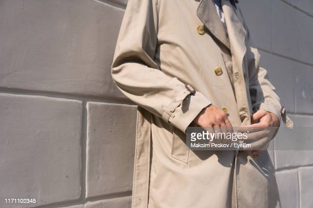 midsection of man wearing trench coat while standing against wall - trench coat stock pictures, royalty-free photos & images
