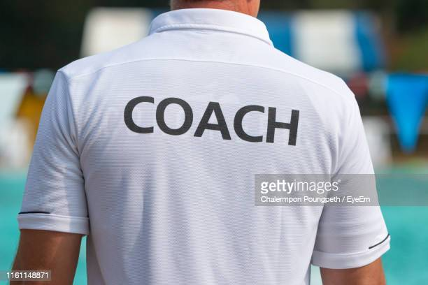 midsection of man wearing t-shirt with coach text standing by swimming pool - all shirts stock pictures, royalty-free photos & images