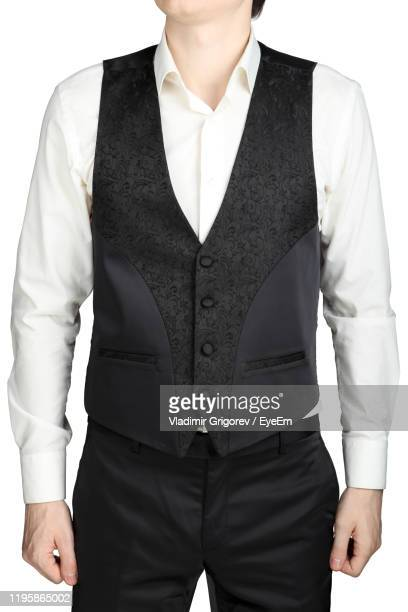 midsection of man wearing tuxedo standing against white background - 男性用ベスト ストックフォトと画像