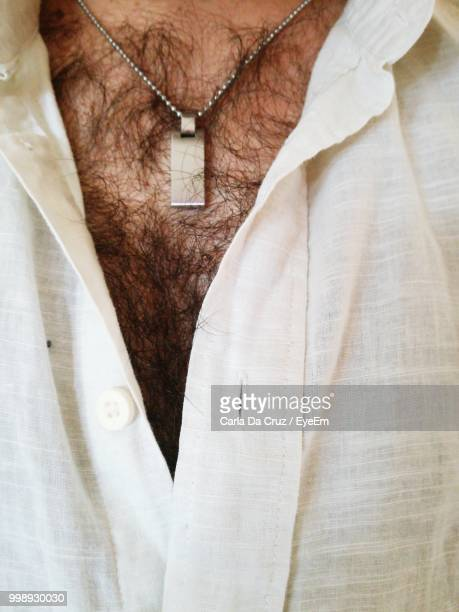 midsection of man wearing white shirt - hairy chest stock-fotos und bilder