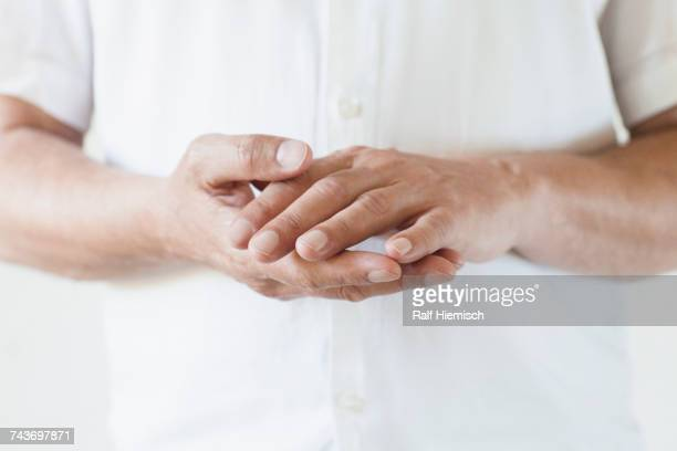 midsection of man wearing white t-shirt with hands clasped - camisa blanca fotografías e imágenes de stock