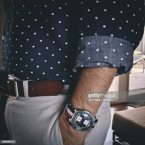 midsection of man wearing wristwatch standing in room - hands in pockets stock photos and pictures