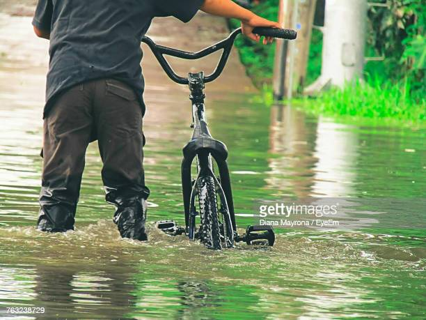midsection of man with bicycle standing in water - flooding stock photos and pictures