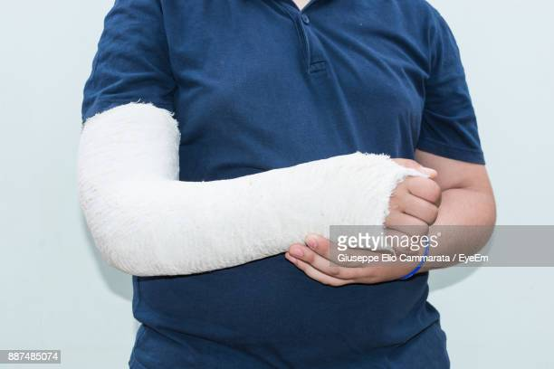 Midsection Of Man With Broken Arm Standing Against White Wall