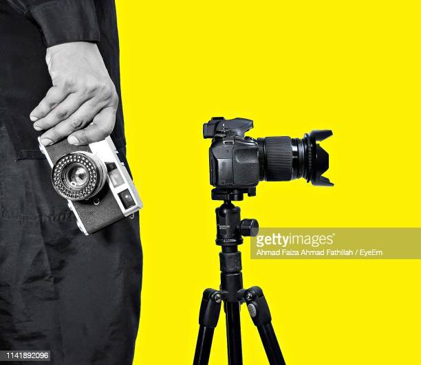 midsection of man with camera standing against yellow background - tripod stock pictures, royalty-free photos & images