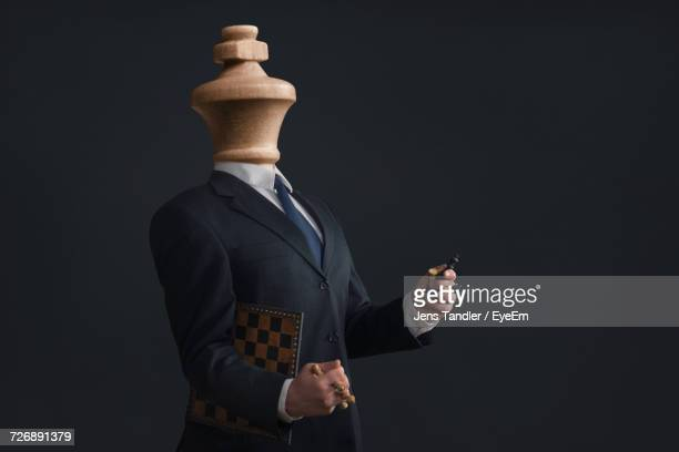 midsection of man with chess piece for a head - chess piece stock pictures, royalty-free photos & images