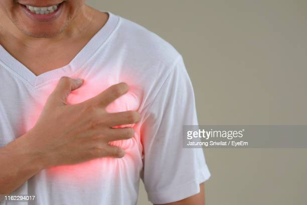 midsection of man with chest pain standing against gray background - heartburn stock photos and pictures
